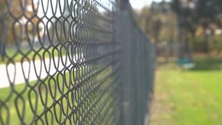 Man walking by fence dragging fingers across mesh 4k