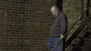Man walking through back street alley looking suspicious 4k