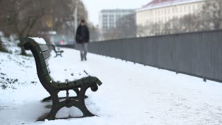 Man walking towards camera on path with snow in city