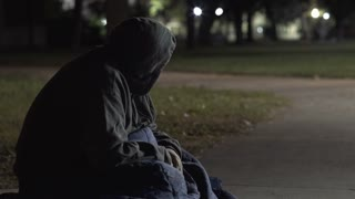 Man with sleeping bag sitting on sidewalk outdoors at night 4k