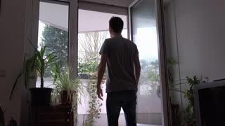 Man yawning at back patio window of apartment 4k