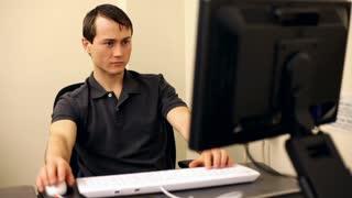 Man yawns while working at computer