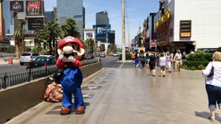 Mario on streets of Vegas waving at pedestrians.
