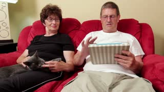 Married couple on couch with cat and tablet