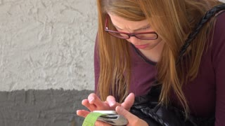 Medium shot of young girl with glasses using cell phone outdoors 4k
