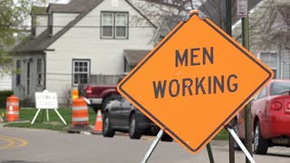 Men working sign in construction area of neighborhood 4k