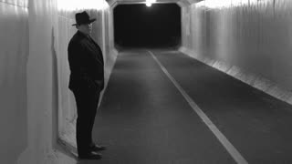 Mobster standing in tunnel waiting