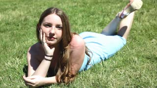Model laying in grass smiling at Camera
