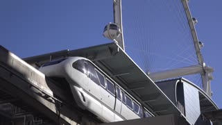 Monorail pulling out of station with High Roller in background 4k