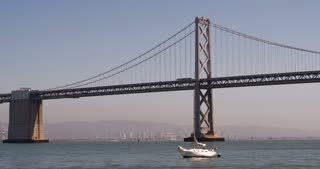 Oakland Bay Bridge with sailboat going by 4k