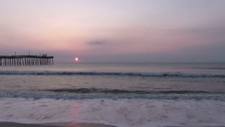 Ocean with Pier and sunset in distance