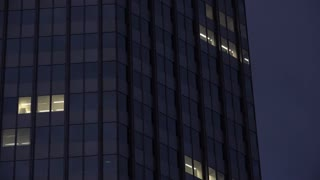 Office building at night with window lights on 4k