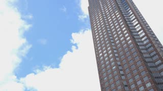 Office building with cloudy blue sky in background 4k