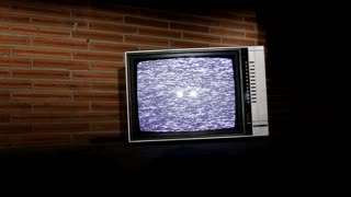 Old Television in front of brick wall