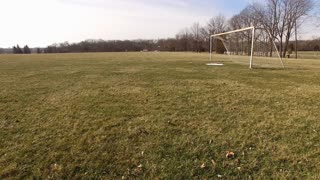 Open field with soccer goal and snow on ground aerial 4k