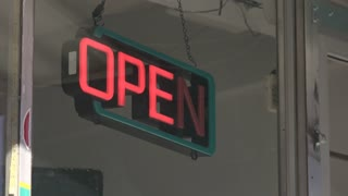 Open sign flashing in store front window 4k