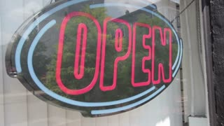 Open sign in store window steadycam shot