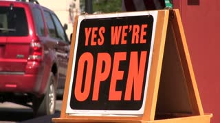 Open sign with customers walking into shop