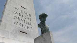 Orville Wright Bust in front of Memorial Pan shot