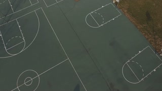 Outdoor basketball courts with kid practicing aerial view 4k