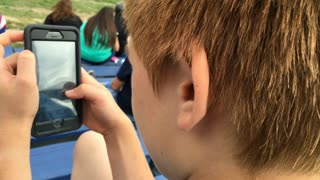 Over the shoulder view of boy using cell phone 4k