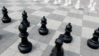Oversized chess pieces fly around