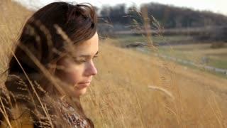 Pan of Girl sitting in Wheat Field