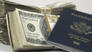 Passport leaning up against stack of money