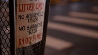Pedestrians crossing street in background of trash can of city 4k