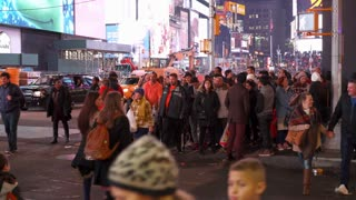 Pedestrians in Times Square at night crossing street 4k
