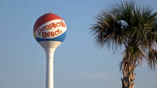 Pensacola Beach water tower with palm tree in foreground 4k