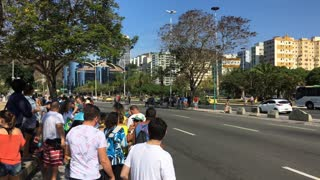 People along streets of Rio Brazil waiting for Olympic torch carrier to run by 4k