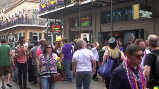 People cheering for beads on Bourbon Street