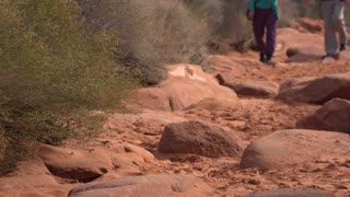 People hiking through dirt path in red mountain dirt 4k