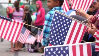People holding American flags along parade route 4k