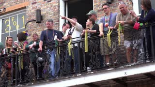 People on Balcony of Bourbon Street with beads