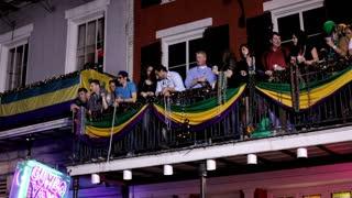 People on balcony throwing beads