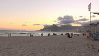 People on beach of Rio de Janeiro with Two Brother Mountain in background 4k