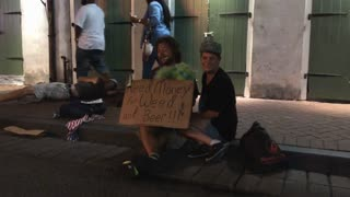 People on Bourbon Street New Orleans with funny sign