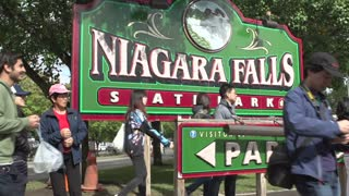 People posing at Niagara Falls sign