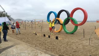 People posing in front of Olympic Rings at Copacabana beach in Rio 4k