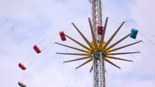 People riding swings at carnival as it raises into sky 4k
