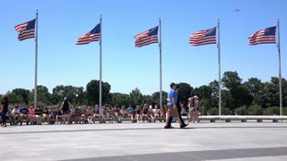 People sitting at base of Washington Monument under US Flags 4k