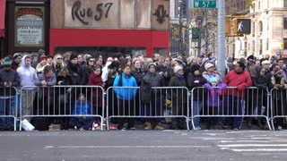 People standing along fence line of Macys parade 2015