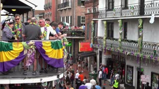 People throwing beads from balcony to Bourbon Street