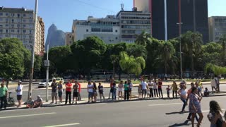 People waiting for Rio Olympics torch carrier to arrive downtown 4k