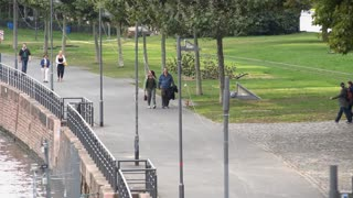 People walking along path by Main river in Frankfurt Germany 4k