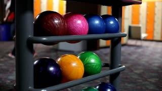 People walking by rack of bowling balls