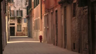 People walking down back street of Venice