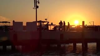 People walking on pier at sunset